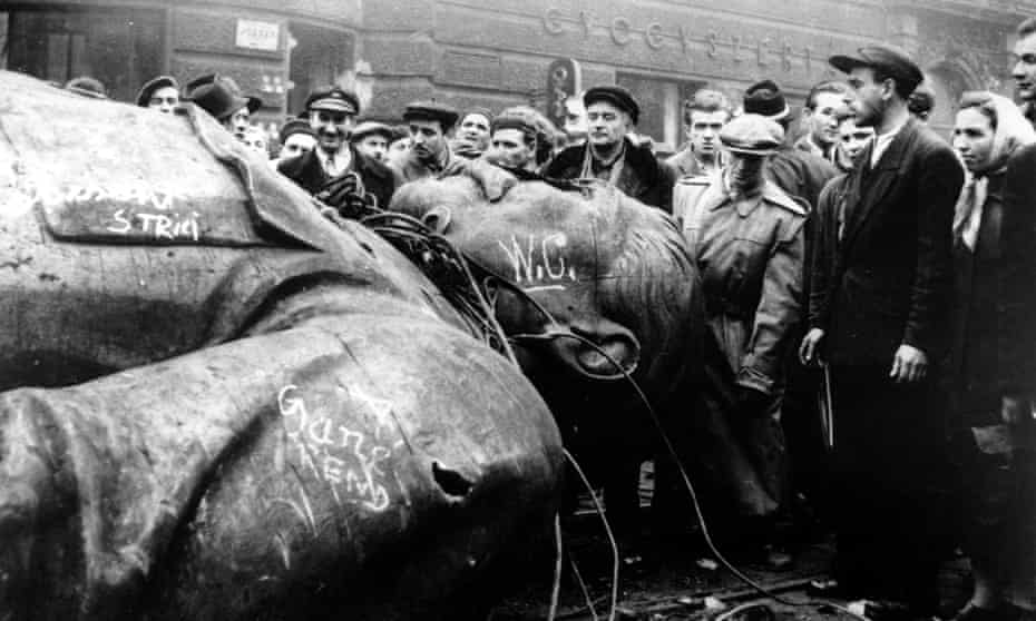 People gather around a fallen statue of Soviet leader Josef Stalin in front of the National Theatre in Budapest, Hungary, 1956.