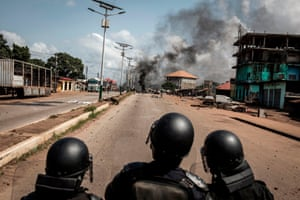 Police officers look on as protesters block the road with burning tyres and wood, during a mass protest the morning after preliminary results were released for five communes in Conakry
