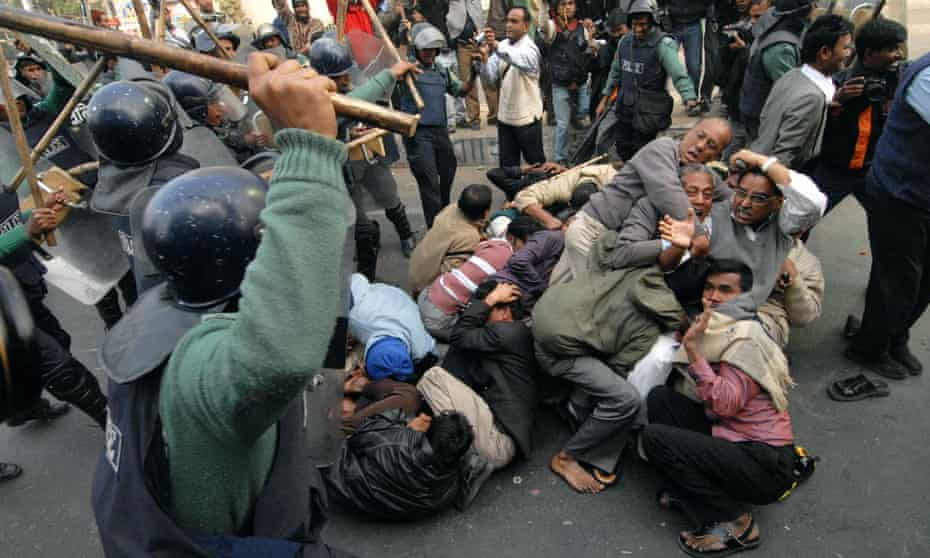 Riot policemen charge a group of activists in  Dhaka, Bangladesh.