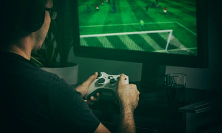 Gamer playing football game with video controller.