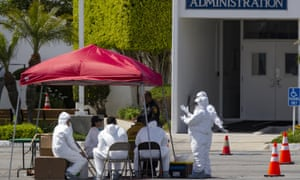 Medical personnel get fitted for testing outside the Crenshaw Christian Center before it opens as a testing site for COVID-19 in South Los Angeles.