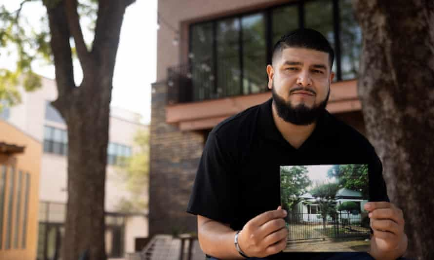 Antonio Vargas with photograph of his childhood home. Vargas's grandfather planted the trees behind him.