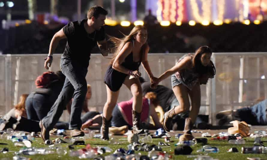 People run from the Route 91 Harvest country music festival in Las Vegas after gunfire was heard on Sunday night.