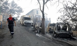 A fireman walks past vehicles that were destroyed by a burning wildfire in Carros, near Nice