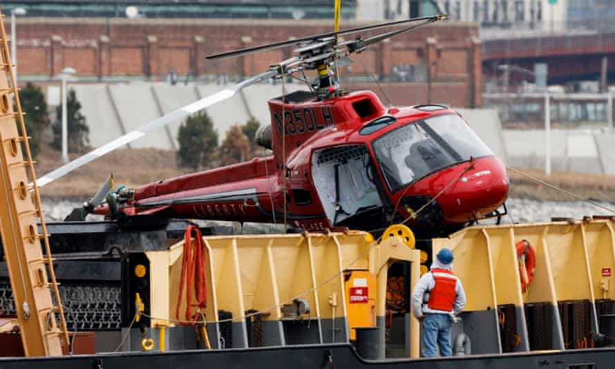A crew member on a crane barge looks at the sightseeing helicopter after it was removed from the East River in New York.