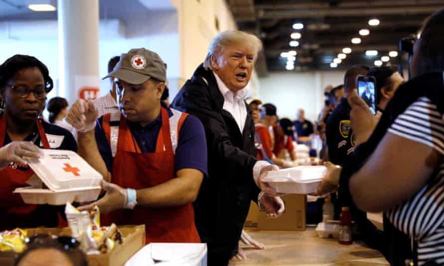 President Trump helps volunteers hand out meals during a visit with flood survivors at a relief center in Houston