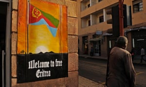A man waits to cross the road beside a patriotic poster in Asmara, Eritrea, on July 18, 2013