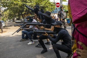 Anti-coup protesters line in formation with homemade air rifles during a demonstration against the military coup in Yangon.