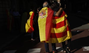 A man draped in a Spanish flag walks with a woman draped in a Catalan flag on their way to the rally.