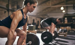 Fit people preparing to deadlift and holding barbells.