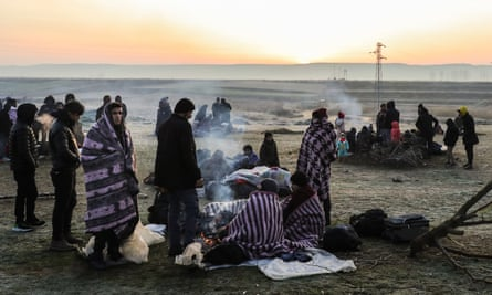Refugees and migrants rest near Pazarkule border as they attempt to enter Greece from Turkey.