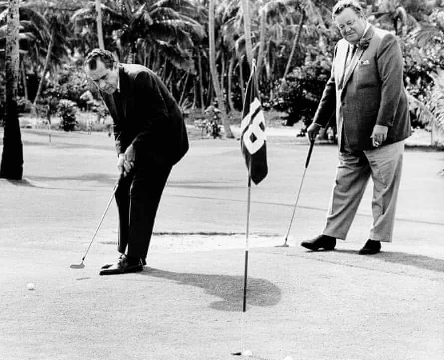 Richard Nixon sinks a putt with comedian Jackie Gleason in 1968.