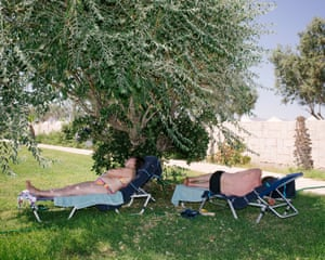 Holidaymakers relax in the shade.