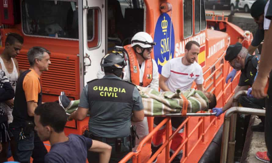 Rescue workers carry an injured Moroccan man on a stretcher at the port of Tarifa, southern Spain