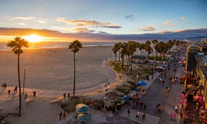 Tourists walking on footpath by beach during sunset. High angle view of Venice beach during sunset.