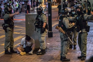 Riot police detain a man after they cleared protesters from an area