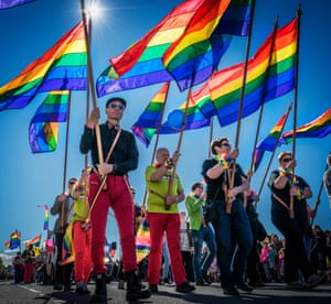 A crowd of people holding rainbow flags in the sun