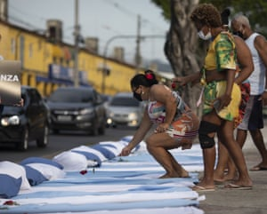 Residents place flowers on mattresses with roses symbolising those who have died of Covid-19, during a protest against the Brazilian government's handling of the pandemic, organised by the Rio de Paz NGO, in front of the Ronaldo Gazolla hospital in Rio de Janeiro.