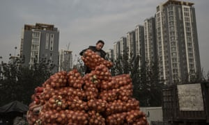 A Chinese market worker unloads onions in Beijing. The economy slowed in the third quarter.