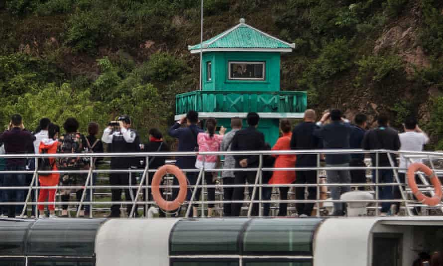Chinese tourists look and take pictures of a North Korean soldier in a watchtower as they ride on a tourist boat on the Yalu river with North Korean territory on both sides, north of the border city of Dandong, Liaoning province, northern China near Sinuiju, North Korea in Dandong, China.