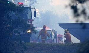 Country Fire Authority officers at Carrum Downs in Melbourne, where a house was badly damaged in a bushfire on Saturday.