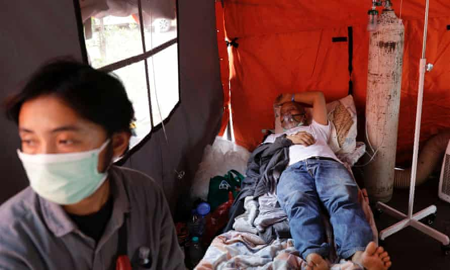 A patient suffering from coronavirus disease rests in a temporary tent outside the emergency ward of a government hospital in Bekasi, on the outskirts of Jakarta, Indonesia