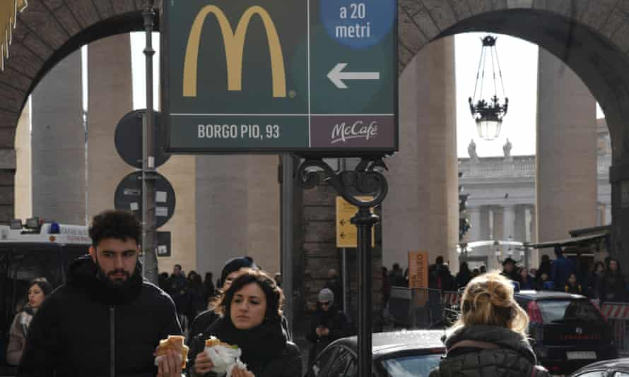A sign pointing the way to a McDonald's restaurant with St Peter's Square in the background