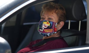 A woman wears a Wonder Woman mask as she waits in line at a Los Angeles Food Bank drive-through.
