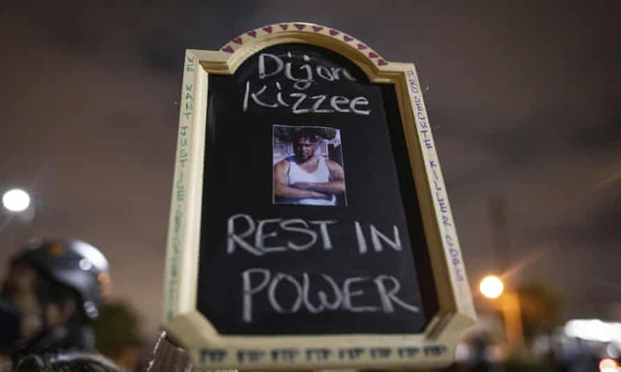 A protester holds a sign with a picture of Dijon Kizzee, who died after being shot by Los Angeles sheriff's department deputies.