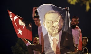 Men hold a banner with a picture of of Recep Tayyip Erdogan in Istanbul.