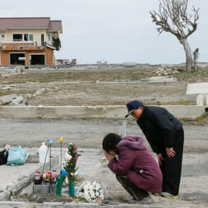 In Namie Seiko Yoshida and her husband Tsutoshi offer a prayer for their late daughter Miki, who was killed by the tsunami while at work at a post office, in Ukedo district, 5km north of the nuclear plant