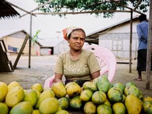 A Rohingya woman sells mangoes at a market stall