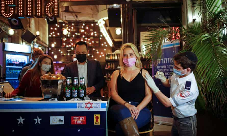 A woman receives a Covid vaccination in Tel Aviv, as part of an initiative offering a free drink at a bar to residents getting the shot