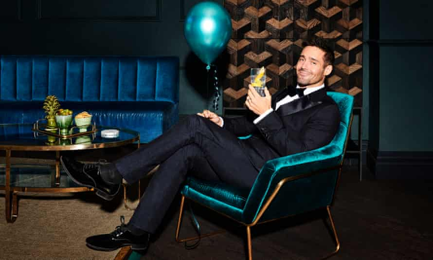 Spencer Matthews, smiling, reclining in a chair with a drink in one hand and a balloon in the other