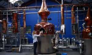 Kit Clancy, an assistant distiller, refills a copper pot still at the Sipmsith gin distillery in London.