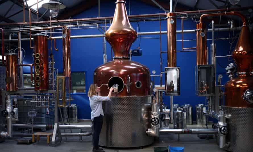 Kit Clancy, an assistant distiller, refills a copper pot still at the Sipmsith gin distillery in London.