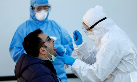 FILE PHOTO: Outbreak of the coronavirus disease (COVID-19) in Rome<br>FILE PHOTO: A health worker wearing a protective gear swabs the mouth of a man outside a mobile logistics unit as the spread of coronavirus disease (COVID-19) continues, in Rome, Italy, April 1, 2020. REUTERS/Yara Nardi - RC2NVF9FDXX6/File Photo