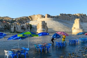 Boys open parasols at a cafe in the Tigris River as the 12,000-year-old ancient city is seen next to the newly built stone wall in Hasankeyf