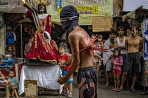 Manila, Philippines: a flagellant whips his bloodied back as penance while walking along a street, after defying government orders to avoid religious gatherings and stay home to curb the spread of coronavirus