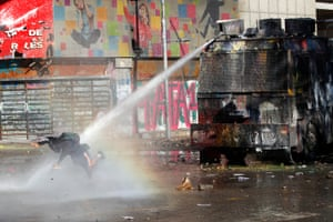 A riot police truck fires water at a demonstrator during a national strike called by trade unions. Santiago, Chile