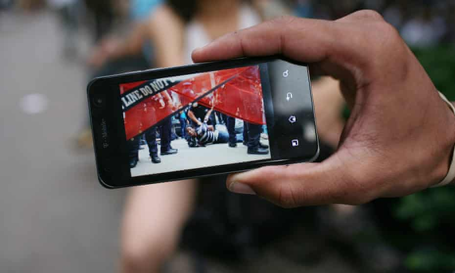 A demonstrator shows a photograph of himself being arrested during the second week of the Occupy encampment.