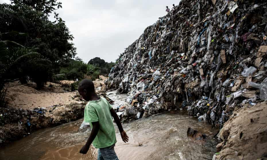 A boy crosses a river whose banks are littered with rubbish in the Kinshasa neighbourhood of Ngaliema.