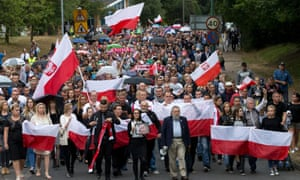Members of the Polish community wave Polish flags as they march through Harlow after the killing of Arkadiusz Jóźwik