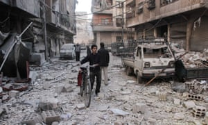 A Syrian boy pushes a bicycle down a street shelled by Syrian government forces.