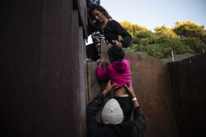 Central American migrants who have been travelling in a caravan hoping to enter the United States, climb the metal barrier separating Playas de Tijuana in Mexico and the US.