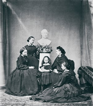 Photograph of Queen Victoria and her daughters clad in black, around a bust of Prince Albert.