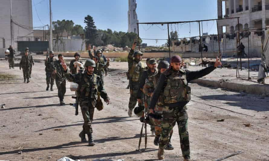 Syrian pro-government soldiers gesture as they walk down a road in eastern Aleppo.