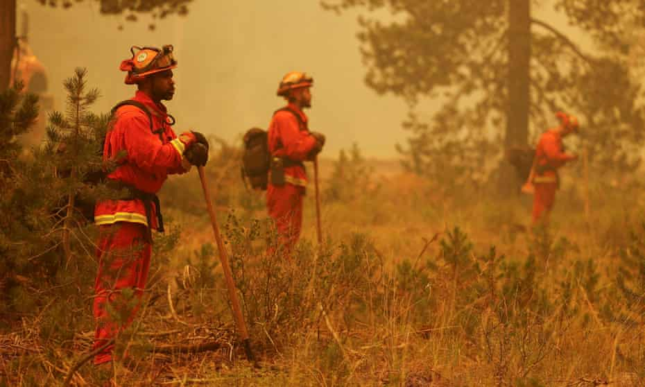 Members of the California corrections department Vallecito fire crew watch for spot fires to slow the spread of the Dixie Fire on Sunday.