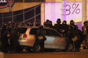 Riot police move a parked car