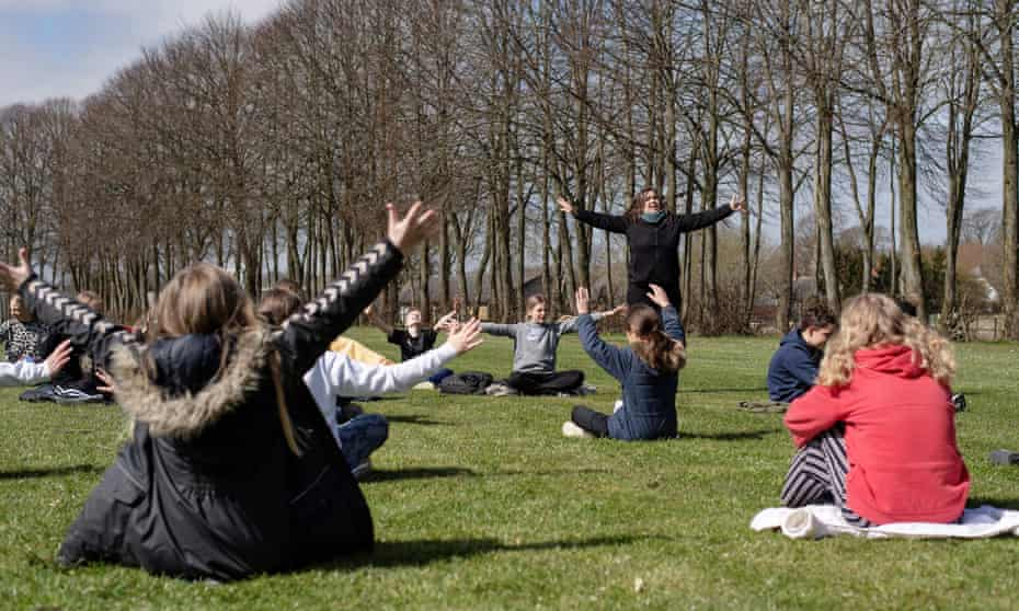 A teacher holds a music lesson outdoors with her class at the Korshoejskolen school, after it reopened following the lockdown due to the coronavirus outbreak, in Randers, Denmark